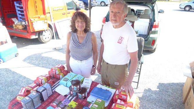 Susan Olsen, left, and Louis Rimbach man the Fair Trade table at the Camden Farmers Market in Salisbury.