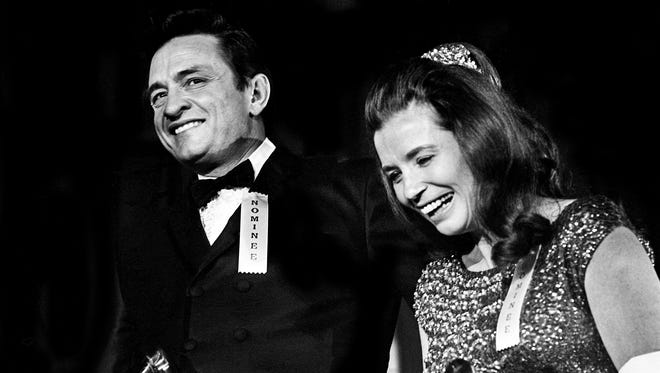 """Johnny and June Carter Cash walk off stage after accepting their awards for Best Country and Western Performance by a Duet, Trio or Group during the 10th annual Grammy Awards show at the National Guard Armory on Feb. 29, 1968. They won for their performance of """"Jackson."""""""