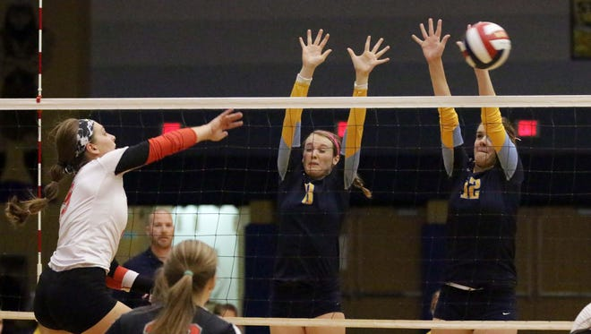 Sheboygan North's Raven Gmach (8) and Sarah Belitz (12) go up for the block on Manitowoc Lincoln's Cassidy Mrotek (9) on Thursday night.
