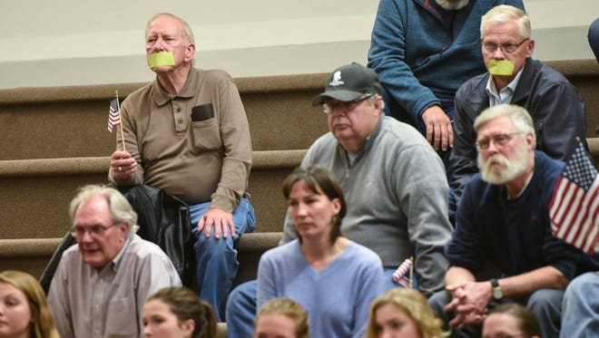 Audience members put tape over their mouths in protest Monday, Nov. 6, during the St. Cloud City Council meeting at City Hall.