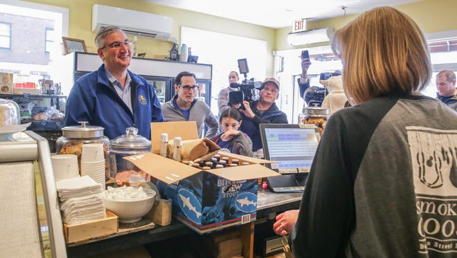 Indiana Governor Eric Holcomb, left, is the first to buy beer on Sunday at noon from Corrie Quinn, right, a manager at Goose The Market in Indianapolis on Sunday, March 4, 2018.