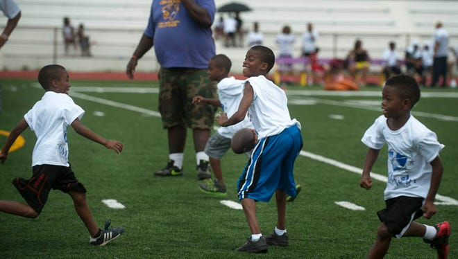 NFL defenseman and Camden native Turk McBride visits a football camp held for city students at the Camden High School football field on Saturday, July 12, 2014.