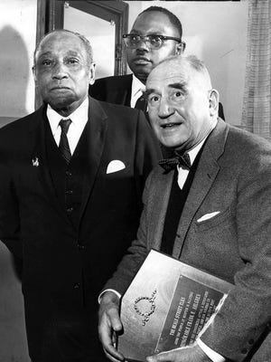"""Frank R. Ahlgren, editor of The Commercial Appeal, held the """"Man of the Year"""" award given him on Jan. 1, 1968, by the Beale Street Elks, as George W. Lee (left), general chairman of the Emancipation Day program, and Rev. S.H. Herring, pastor of the St. Paul Baptist Church look on."""