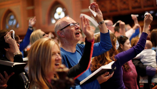 Marathon runner Joe Warfield of Oklahoma City participates in an Easter service at the Old South Church on Sunday in Boston. Runners received a blessing one day before the 118th Boston Marathon.