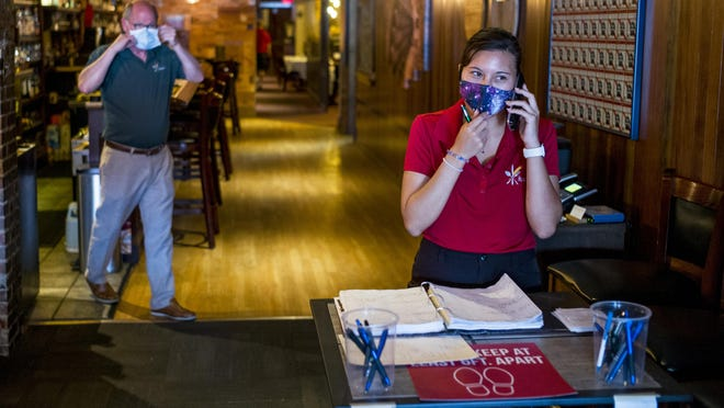 Becky Welch takes a reservation for inside lunch dining as Hearth restaurant owner Hugh Higgins dons his mask Friday, June 26, 2020 in Peoria Heights.