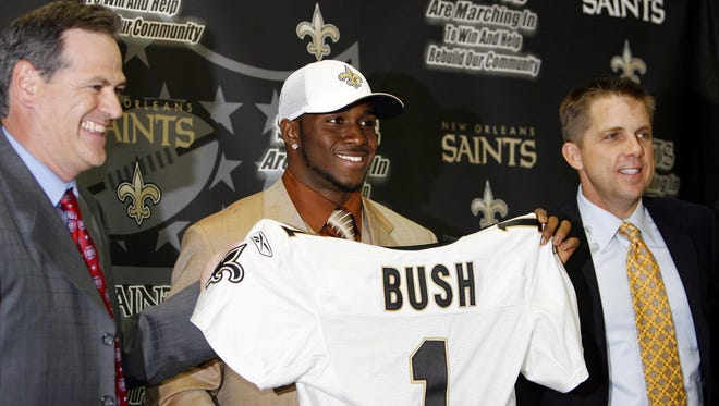 The New Orleans Saints newest player Reggie Bush, center,  holds up a jersey with Saints general manger Mickey Loomis, left, and head coach Sean Payton, right, at their headquarters in Metairie, La., on Saturday, April 29, 2006. The Saints had the second pick overall  and they took  runningback Bush.(AP Photo/Alex Brandon)