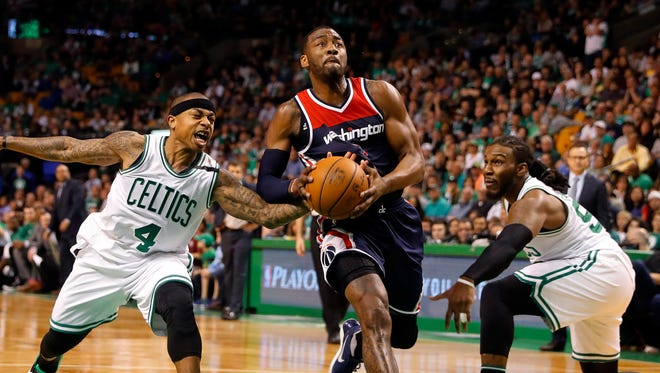 Boston Celtics guard Isaiah Thomas (4) reaches in to try to steal the ball from Washington Wizards guard John Wall (2) as he goes by Boston Celtics forward Jae Crowder (99) during the second quarter in game one of the second round of the 2017 NBA Playoffs at TD Garden.