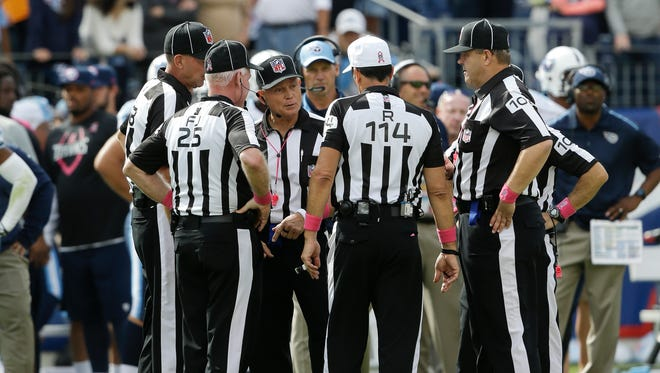 Officials confer in the second half of an NFL football game between the Tennessee Titans and the Cleveland Browns Oct. 5 in Nashville, Tenn.