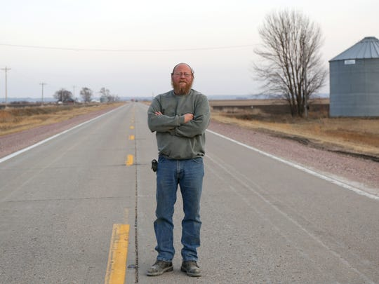 Bruce Nance, who owns a body repair shop on Highway 141 south of Sioux City, stands on the highway near the site of a fatal accident that happened in late November, and killed five.