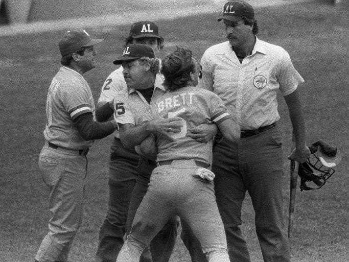 Kansas City's George Brett, center, is restrained by umpire Joe Brinkman after his bat, held by umpire Tim McClelland, was ruled illegal because of pine tar beyond the legal limit on the handle in this July 24, 1983 photo at Yankee Stadium in New York. Brett hit a home run that would have won the game against the Yankees, but was instead called out. Royals manager Dick Howser, left, argues on his teams behalf.