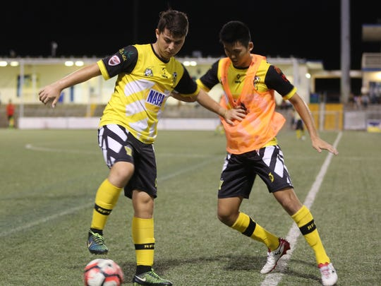 NAPA Rovers D2's Shawn Spindel keeps back NAPA Rovers' Takumi Ito to stay in control of the ball in a quarterfinal match of the Bank of Guam 10th Annual GFA Cup Friday evening at the Guam Football Association National Training Center. NAPA Rovers won 5-0 over their D2 counterparts.