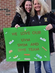 Krista Balogh, left, and Amy Stannard hold a sign in