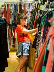 A customer browses the aisles at Dirt Chic, a consignment