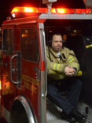Fire Chief Dave Schmaltz rides a fire engine to a call