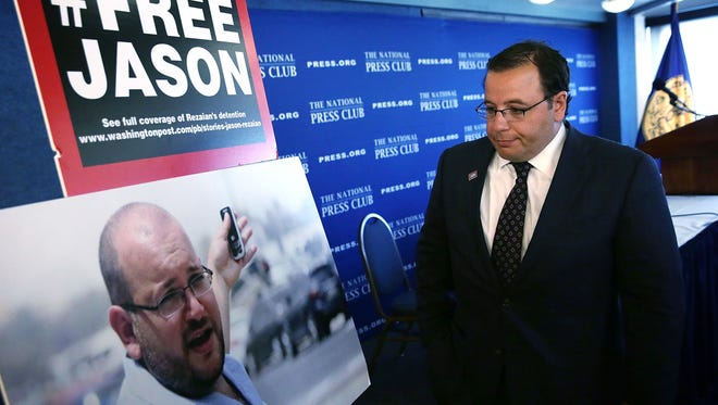 Ali Rezaian looks at a picture of his brother, Washington Post Tehran bureau chief Jason Rezaian, after a news conference at the National Press Club July 22, 2015, in Washington, DC.