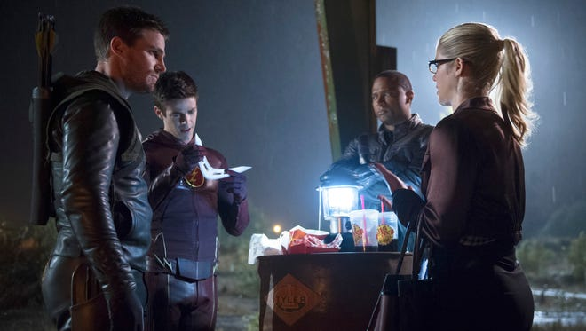 """Oliver Queen (far left, Stephen Amell), Barry Allen (Grant Gustin), John Diggle (David Ramsey) and Felicity Smoak (Emily Bett Rickards) investigate a boomerang over a meal of Big Belly Burger in Tuesday's episode of """"The Flash."""""""