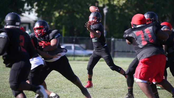 Wilson quarterback James Cotton looks to pass as he rolls out of the pocket during their practice Monday, Aug. 29, 2016 in Rochester.
