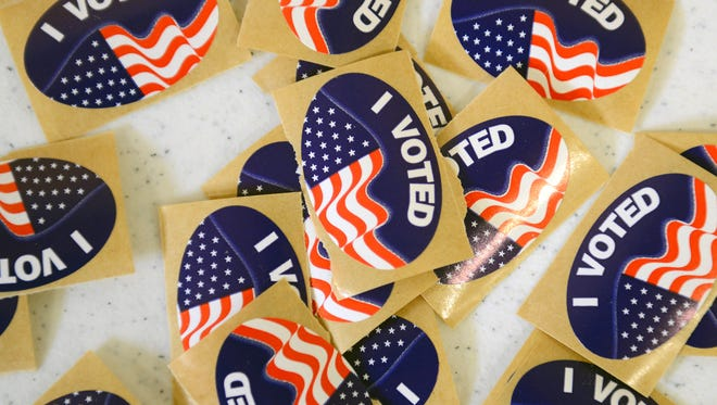 """A pile of """"I Voted"""" stickers sit on a table for voters at Riverview church in Delta Township for Michigan's primary election in March."""