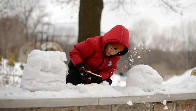 Max Jiang, 4, of De Pere, plays with snow while attending the Winter Family Festival at the Green Bay Botanical Garden in Green Bay on Saturday.