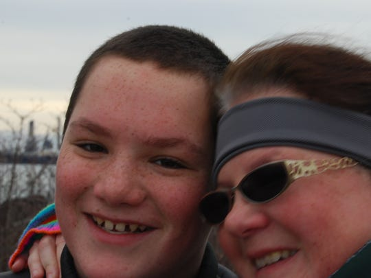 Jonathon Beerbower, 13, gets a hug from his mom, Cindy, Saturday at the Blue Water River Walk.