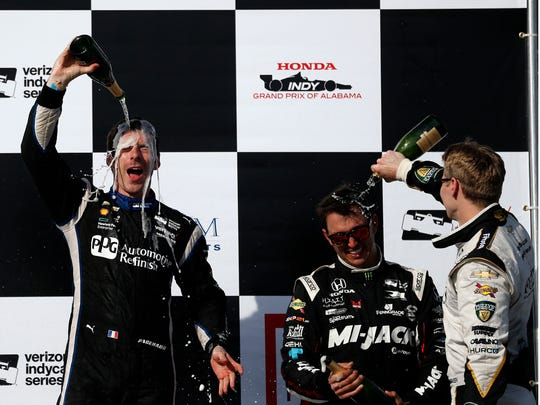 Simon Pagenaud, of Montmorillon, France, left, pours champagne over himself to celebrate with Graham Rahal of New Albany, Ohio, center, and Josef Newgarden, of Hendersonville, Tenn., after the Indy Grand Prix of Alabama auto race, Sunday, April 24, 2016, in Birmingham, Ala.