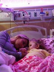 Adrianna Fritts and her mother, Dava Wahl, curl up together in her bed at Children's Hospital. Adrianna, 1, is battling brain cancer.
