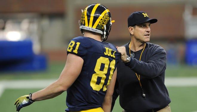 University of Michigan coach Jim Harbaugh  runs plays with tight end Michael Jocz.