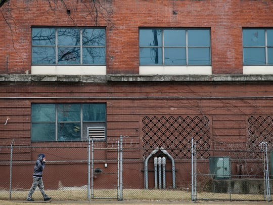 A man walks past the old Queensgate Correctional Facility on Linn Street Wednesday February 14, 2018. The jail closed in 2008 could provide a good solution to jail overcrowding according to Sheriff Jim Neil, When the county closed the Queensgate jail it housed more than 800 prisoners.