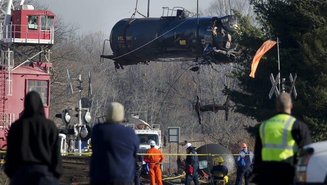 A crane raises up the second submerged tanker from the Paulsboro train derailment site over Mantua creek on Friday, December 14, 2012.