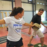 Maggie Kassenbrock, 15, who plays softball year round , works with coach Keith Smith at Champions Edge training facility in Indianapolis.