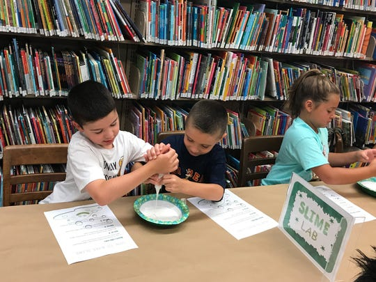 Parker Sabia, 9, at left, and Rocco Caputo, 7, squeeze the glue into their bowl as one step to make slime at the Cedar Grove Library on July 14, 2017.