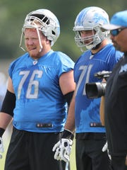 Lions guard T.J. Lang, left, and tackle Rick Wagner watch drills during practice Sunday, July 30, 2017 in Allen Park.