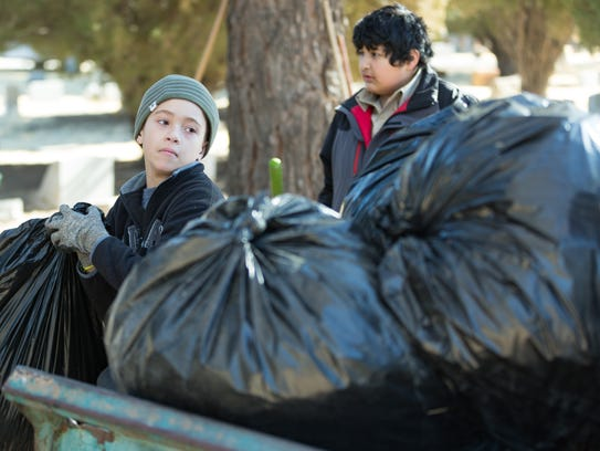 Jayden Purvis, 13, left, and Lazaro Quezada, 11, help with Gunnar Smith's Eagle Scout Service Project on Saturday, January 27, 2018 at Masonic Cemetery.