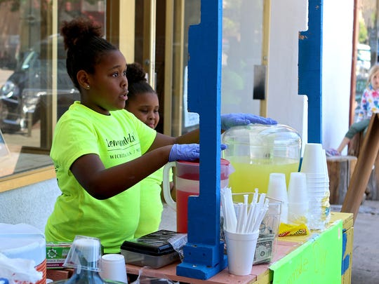 Antoinae Rankin (left) and A'nya Rankin talk with customers about what products they have available at the Sweettooth Lemonade stand during the Wichita Falls Lemonade Day in 2017.