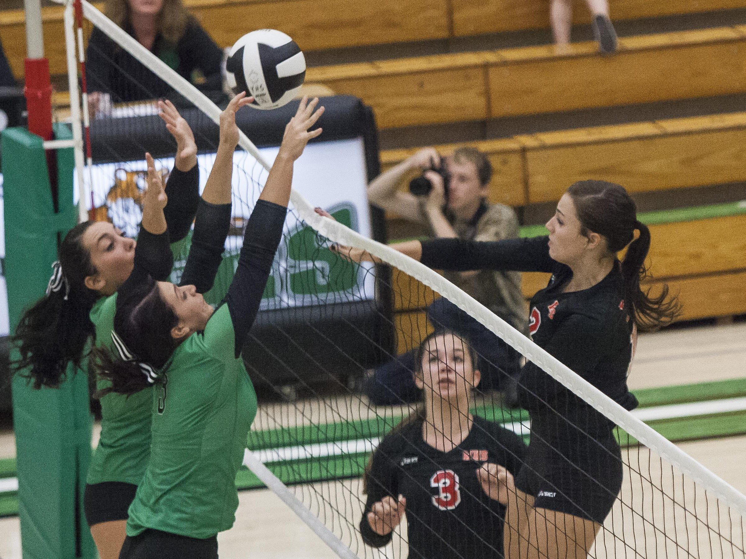 Yorktown's Rhyen Neal and Kendall Murr attempt to block Wapahani's Chase Curry on Tuesday night.