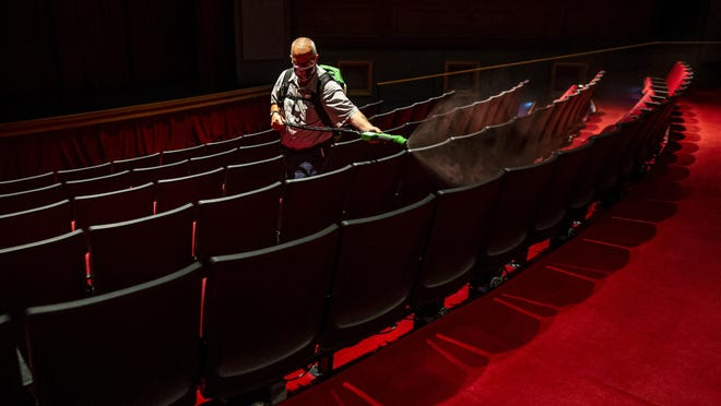 Terry Rutherford, with the ALPLM Building and Grounds crew, uses a sprayer to apply disinfectant to the seats of the Union Theater at the Abraham Lincoln Presidential Museum as they prepare to reopen to the public during the COVID-19 pandemic, Tuesday, June 30, 2020, in Springfield, Ill. At the beginning of each day and between each showing in the theaters a member of the staff will be spraying down the area with disinfectant.
