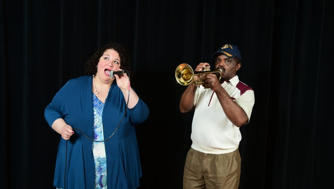 """Charles Okereke, who wrote the song """"Trump Up America,"""" and singer Lisa Muehlbauer pose for a photo during a recording session. The trumpet is a prop."""