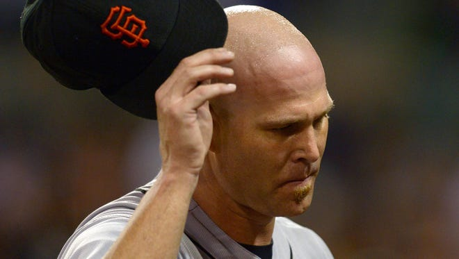 Tim Hudson reacts as he walks to the dugout after being relieved during the fifth inning.