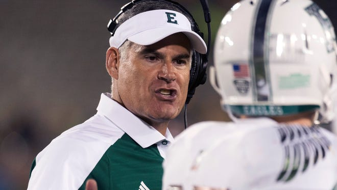 In this Sept. 10, 2016, file photo, Eastern Michigan head coach Chris Creighton, left, talks to wide receiver Mathew Sexton during the third quarter of an NCAA college football game against Missouri, in Columbia, Mo.