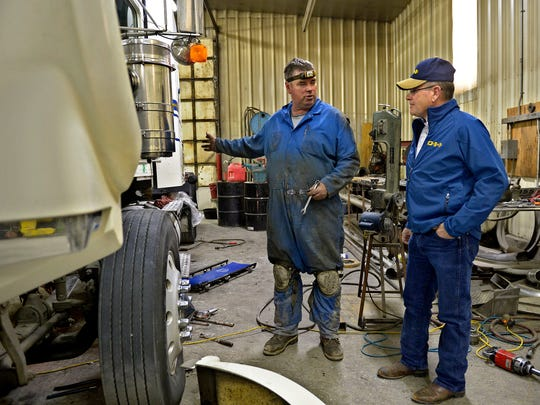 Mike Irvin, right, co-owner of Dave Irvin Inc., in Shelby talks with mechanic Kolin Rice. Irvin says there has been a particulary big demand for truck drivers and mechanics since the development boom in the Bakken oilfield.