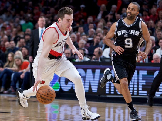 Portland Trail Blazers guard Pat Connaughton, left, dribbles past San Antonio Spurs guard Tony Parker during the first half of an NBA basketball game in Portland, Ore., Monday, April 10, 2017. (AP Photo/Craig Mitchelldyer)