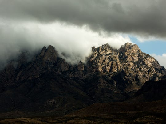 Clouds roll over the tops of the Organ Mountains as seen from the entrance of Dripping Springs Natural Area.The Organ Mountains-Desert Peaks National Monument includes the Organ Mountains, Desert Peaks, Potrillo Mountains and Doña Ana Mountains.