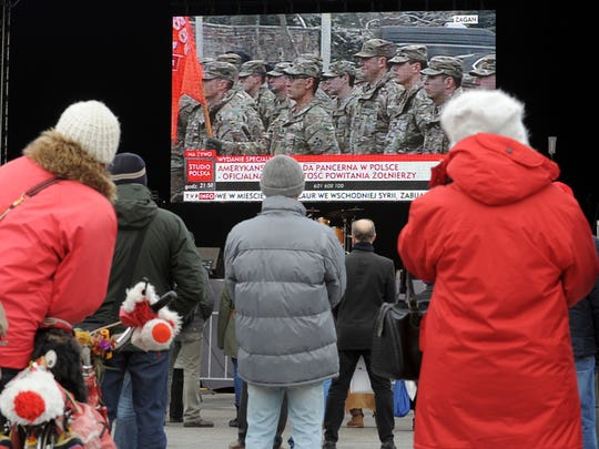 People watch a live transmission of the official welcoming ceremony of U.S. troops in Poland held in Zagan, during a military picknic, in Warsaw, Poland, Saturday, Jan. 14, 2017. The Polish government organized military events across the country to mark the arrival of the Americans from Fort Carson, Colorado.