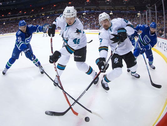 San Jose Sharks' Tomas Hertl, center left, of the Czech Republic, and Joonas Donskoi, centrt right, of Finland, reach for the puck in front of Vancouver Canucks' Michael Chaput, left, and Luca Sbisa, of Italy, during the first period of an NHL hockey game Sunday, April 2, 2017, in Vancouver, British Columbia. (Darryl Dyck/The Canadian Press via AP)