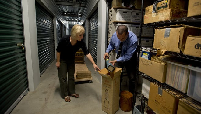 Professional organizer Claudia Smith helps Alan Miller sort through, organize and pare down a storage unit that contains memorabilia once owned by his parents in Davis, Calif.