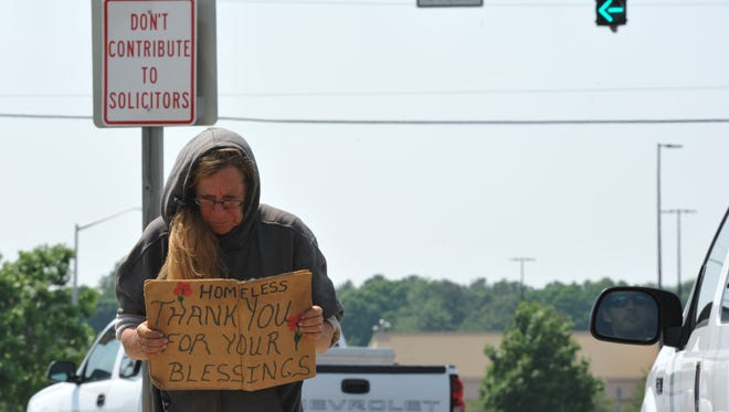 """A homeless woman asks for donations at the entrance to The Commons near Route 13 as a sign behind her reads """"Don't Contribute to Solicitors"""" that is posted at the entrance way to The Commons near Route 13."""