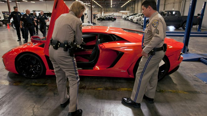"""California Highway Patrol officers Lt. Glenda Brents, left, and Sgt. Mike Stefanoff check a suspected stolen 2012 Lamborghini Aventador LP700-4 """"supercar"""" in this 2012 file photo."""