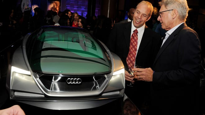 Actor Harrison Ford. right,  views a model of the Audi used in the film at the after party for the premiere of Summit Entertainment's 'Ender's Game.'