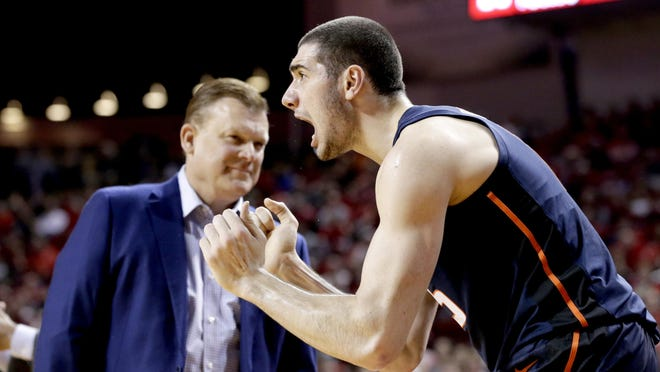 Illinois' Giorgi Bezhanishvili, right, cheers for the team in front of Illinois coach Brad Underwood during a game against Nebraska in Lincoln, Neb.
