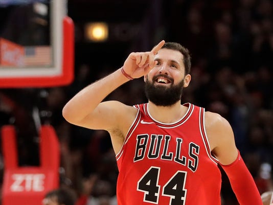 Chicago Bulls' Nikola Mirotic celebrates as his team pulls away from the Philadelphia 76ers during the second half of an NBA basketball game Monday, Dec. 18, 2017, in Chicago. (AP Photo/Charles Rex Arbogast)